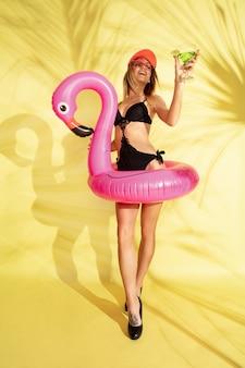 Mulher posando com um macacão da moda e um flamingo rosa
