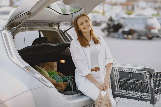 Mulher posando com uma sacola de compras por seu carro