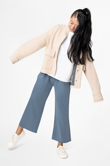 Mulher posando de jaqueta bege e calça azul casual wear