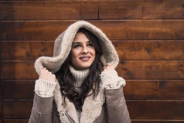 Mulher posando e segurando capuz em frente a uma parede de madeira no tempo frio.