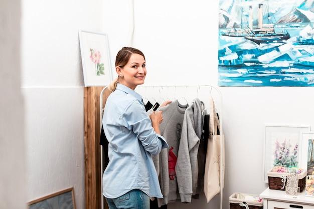 Mulher posando e sorrindo com roupas
