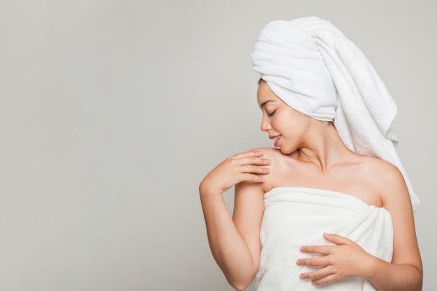 Mulher posando e tocando seu ombro