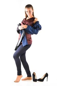 Mulher posando em pé descalça e segurando uma legging nas mãos