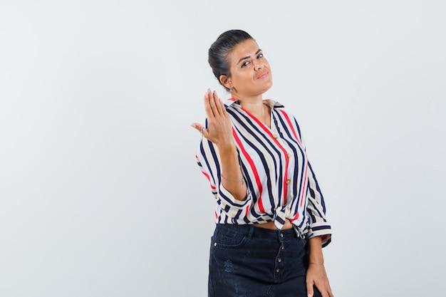 Mulher posando enquanto levanta a mão na camisa, saia e parece confiante