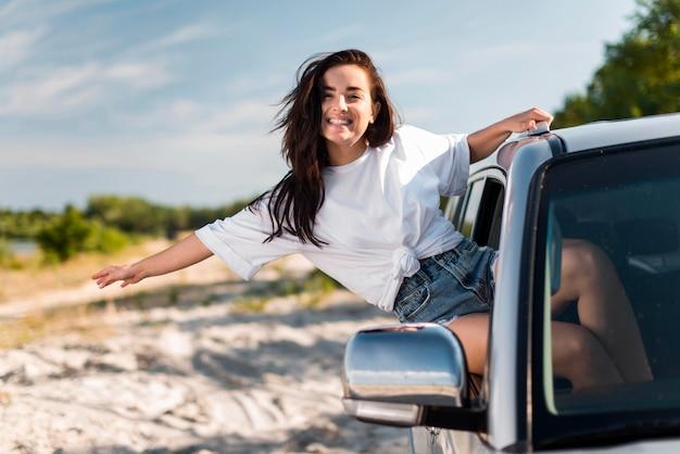 Mulher posando enquanto se inclina na janela do carro