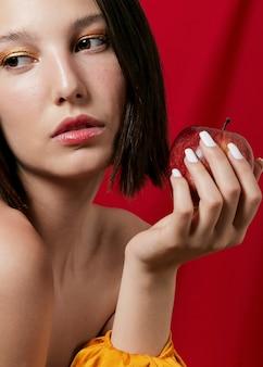 Mulher posando enquanto segura uma maçã