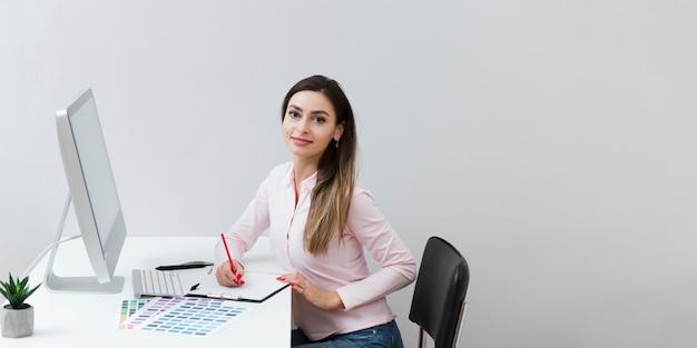 Mulher posando enquanto trabalha no computador