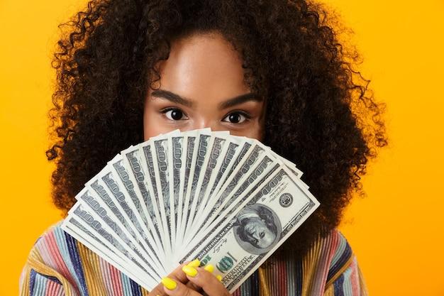 Mulher posando isolado sobre o espaço amarelo, segurando o dinheiro cobrindo o rosto.