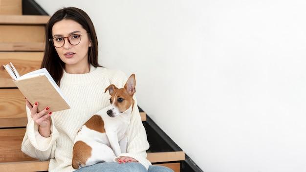 Mulher posando na escada com livro e seu cachorro