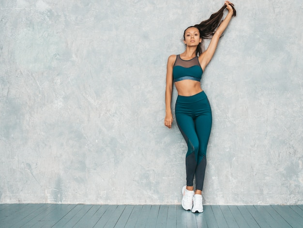 Mulher posando no estúdio perto da parede cinza