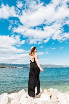 Mulher posando no lindo dia ao lado do oceano