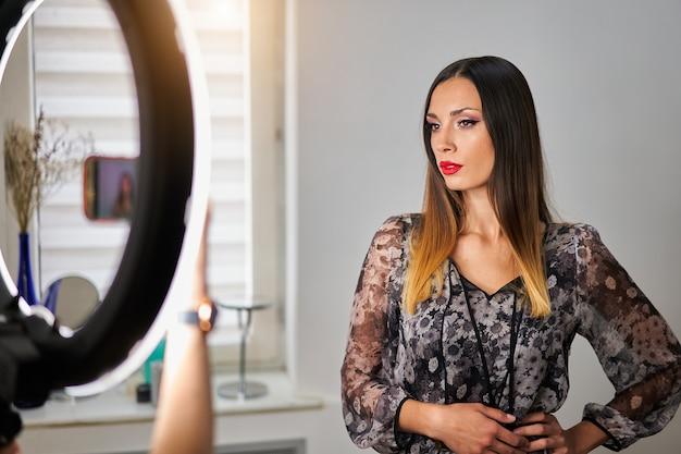 Mulher posando para foto em smartphone com anel de luz mostrando resultado de maquiagem