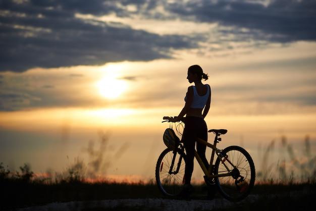 Mulher posando perto de bicicleta e natureza enoying.