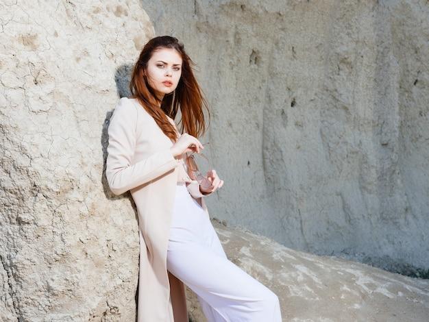 Mulher posando perto de pedras na moda estilo de vida de areia. foto de alta qualidade