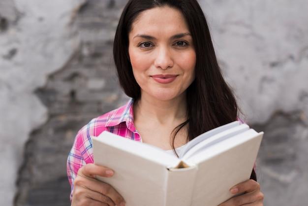 Mulher positiva close-up, segurando um livro