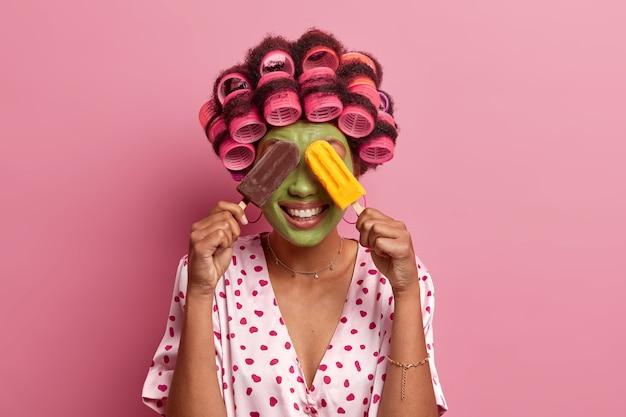 Mulher positiva cobre os olhos com dois deliciosos sorvetes, sorri feliz, aplica máscara facial verde e rolos de cabelo, vestida com manto casual, posa