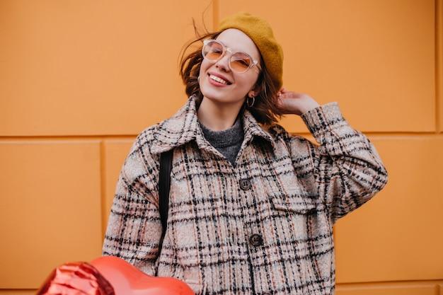 Mulher positiva com casaco de tweed com sorriso posando na parede laranja