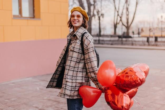 Mulher positiva com casaco xadrez sorrindo contra a parede da cidade
