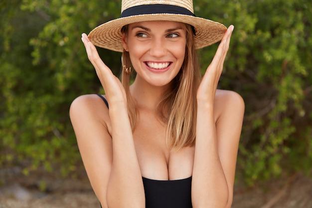 Mulher positiva com chapéu de verão parece feliz, usa maiô preto e respira o ar marinho fresco. jovem relaxada aproveita as férias de verão na costa