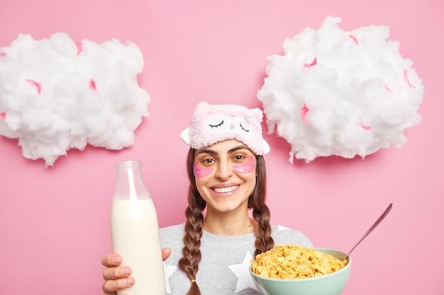 Mulher positiva com duas tranças indo tomar café da manhã come cereais com leite e sorri delicadamente vestida com pijamas