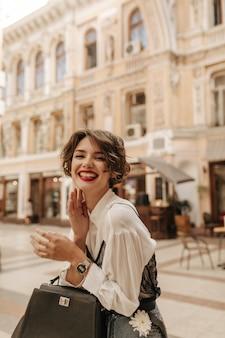 Mulher positiva com lábios vermelhos brilhantes e cabelos ondulados, rindo na cidade. mulher legal na camisa branca com bolsa, posando na rua.
