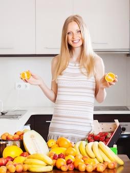 Mulher positiva com laranjas e outras frutas