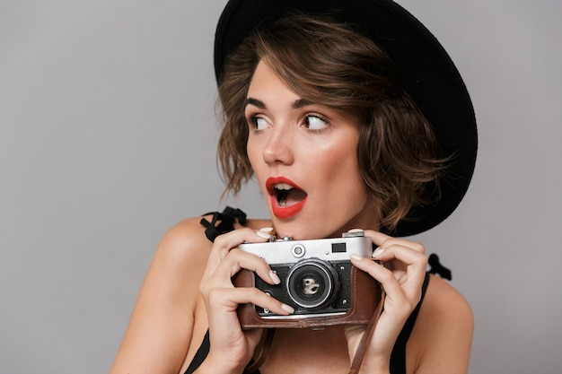 Mulher positiva com vestido preto e chapéu segurando uma câmera retro, isolada sobre uma parede cinza