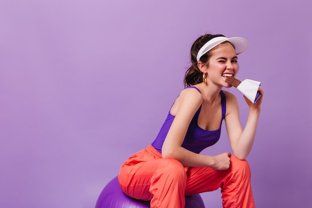 Mulher positiva de cabelo escuro com chapéu a comer barra de chocolate