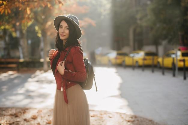 Mulher positiva de cabelos escuros com chapéu relaxando no parque outono