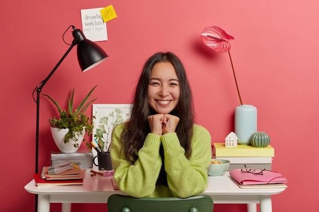 Mulher positiva de cabelos escuros com sorriso agradável, mantém as mãos embaixo do queixo, estuda em casa na área de trabalho, se prepara para os próximos exames, isolada sobre o fundo rosa