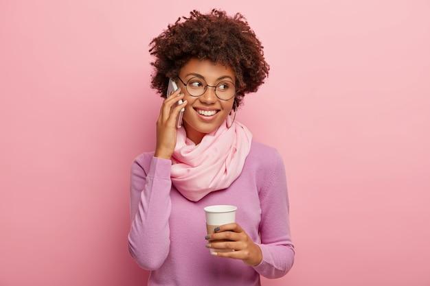 Mulher positiva de pele escura com corte de cabelo afro, fala pelo celular, segura café para viagem, gosta de uma conversa agradável, usa blusão casual e lenço de seda, sorri amplamente, discute algo