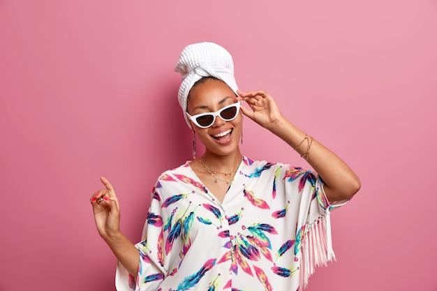 Mulher positiva de pele escura vestida com vestido doméstico usa óculos de sol, toalha de banho na cabeça, sente-se revigorada após tomar banho, pele saudável, sorrisos e dança amplamente sobre a parede rosa estando em casa