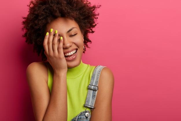 Mulher positiva e despreocupada toca seu rosto, ri sinceramente, ouve uma história engraçada