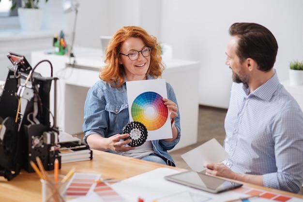 Mulher positiva e simpática encantada segurando uma paleta de cores e mostrando a ele enquanto escolhem a cor juntos