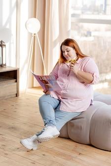 Mulher positiva e simpática lendo sobre beleza enquanto está sentada com uma banana na mão