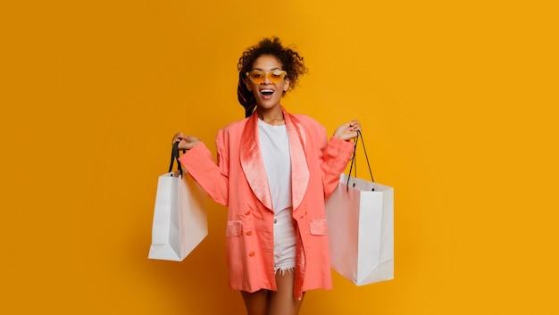 Mulher positiva elegante com pele escura segurando sacolas, de pé sobre fundo amarelo.