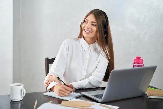 Mulher positiva em fones de ouvido, estudando no laptop