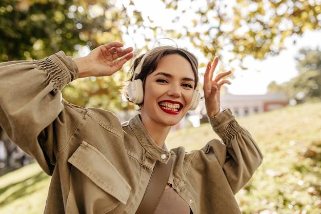 Mulher positiva em jaqueta jeans verde-oliva e fones de ouvido brancos, sorrindo do lado de fora. mulher de cabelo curto com lábios vermelhos se diverte ao ar livre.