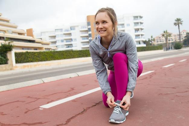 Mulher positiva em leggings de pé sobre um joelho e amarrar rendas
