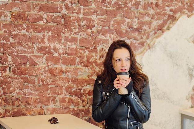 Mulher positiva em roupas elegantes bebendo bebida para viagem enquanto está sentado à mesa na rua perto do café durante o dia