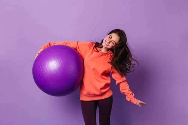 Mulher positiva em um terno esportivo brilhante está envolvida em atividades físicas