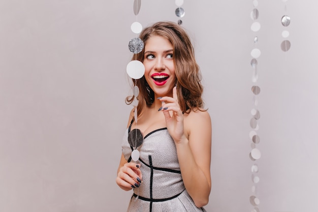 Mulher positiva em um vestido brilhante olha pensativa, posando entre um cenário brilhante na parede branca.