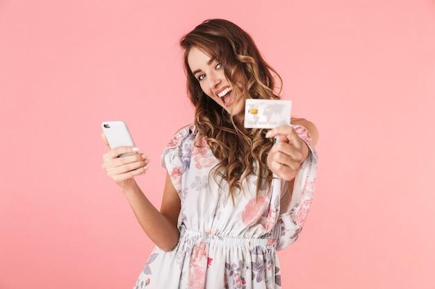 Mulher positiva em vestido segurando smartphone e cartão de crédito, isolado em rosa