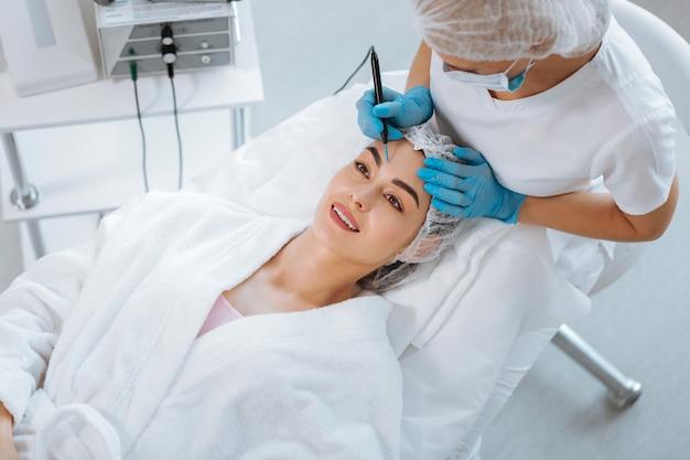 = mulher positiva encantada sorrindo enquanto se sente feliz com o procedimento de cosmetologia