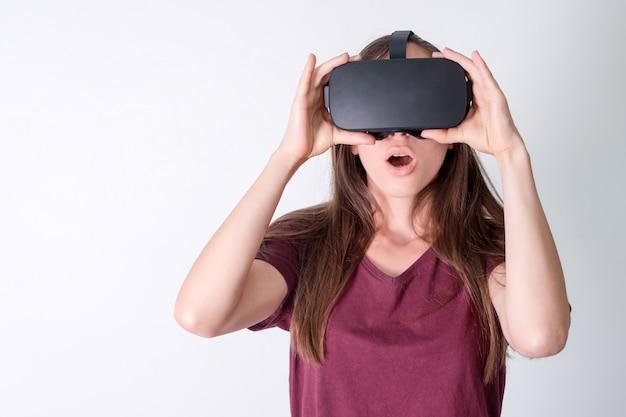 Mulher positiva espantada usando realidade virtual óculos fone de ouvido, caixa vr. conexão, tecnologia, nova geração, conceito de progresso. menina surpreendida por algo na realidade virtual. estúdio filmado em cinza