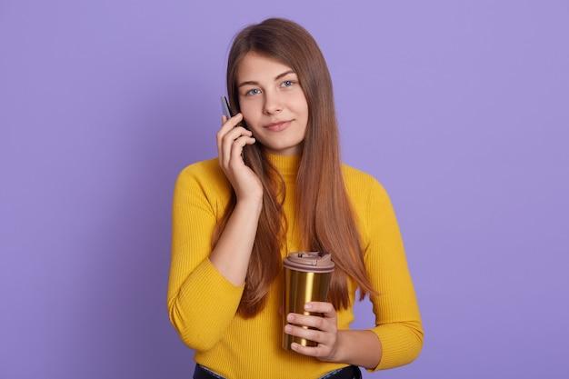 Mulher positiva fala com interesse e alegria via celular, usa traje casual, gosta de beber café aromático em caneca térmica, isolado sobre o fundo lila, senhora olha para a câmera.