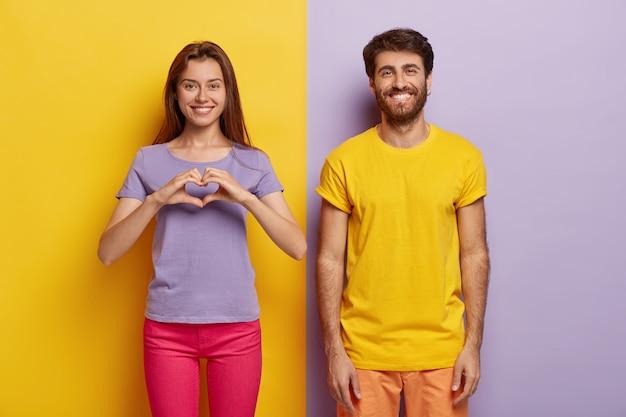 Mulher positiva faz gestos de coração, expressa amor e bons sentimentos, o namorado está perto com um sorriso dentuço