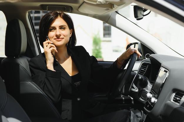 Mulher positiva feliz sorrindo enquanto aperta o cinto de segurança usando o telefone