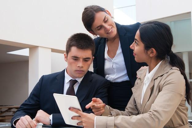 Mulher positiva mostrando a tela do tablet para pessoas de negócios