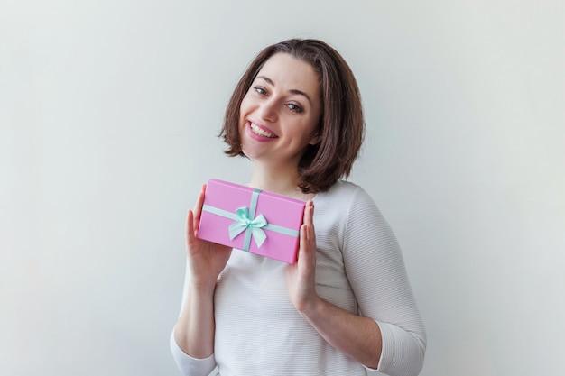 Mulher positiva nova que mantem a caixa de presente cor-de-rosa pequena isolada no branco. preparação para férias. menina olhando feliz e animado